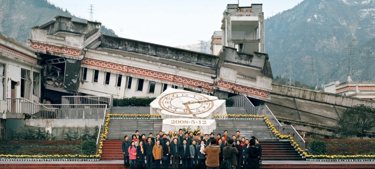 Tourists pose for a photo in front of the remains of a building destroyed in the 2008 Earthquake in China's Wenchuan Special Tourism Zone